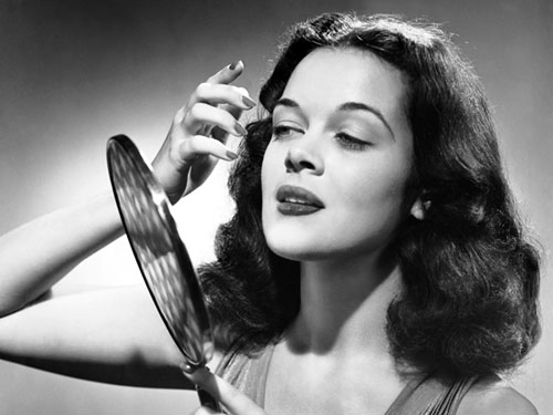 Retro woman looking into a hand mirror